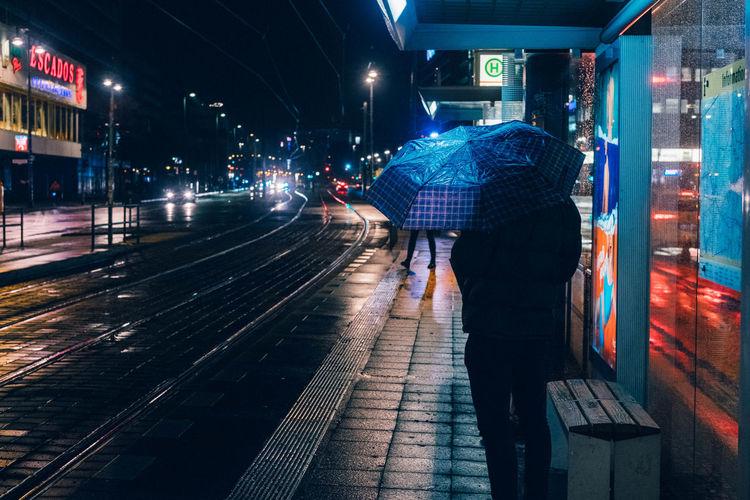 Man standing on railroad station platform at night