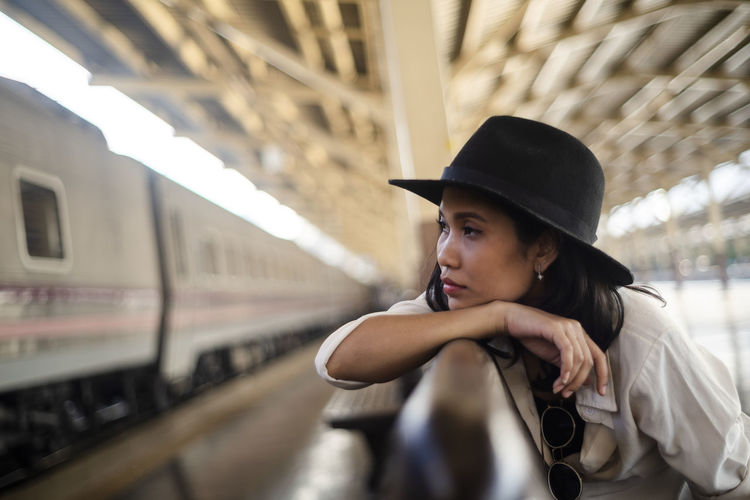 Portrait of young woman looking away at railroad station