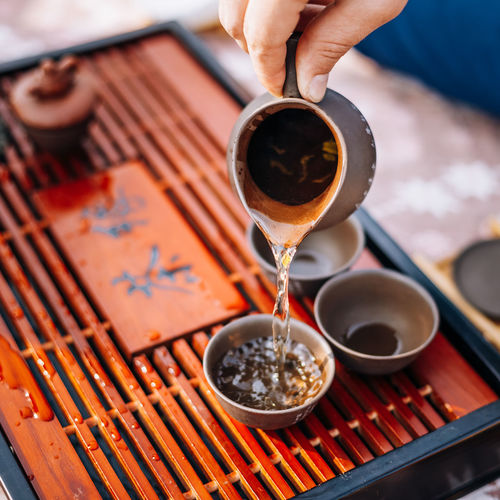 Close-Up Of Hand Pouring Tea From Pitcher On Table