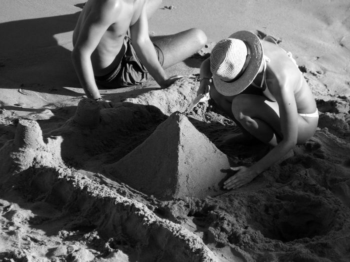 Man and woman preparing sandcastle at beach