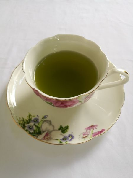 A cup of green tea isolated on white background. Tea - Hot Drink Tea Cup Green Tea Drink Food And Drink Teabag Studio Shot No People Indoors  Tea Ceremony High Angle View Green Color Japanese Tea Cup Healthy Eating Herbal Tea White Background Freshness Close-up Day