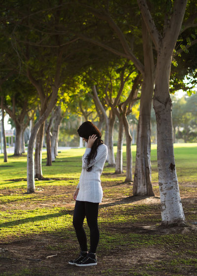 Young woman standing in the tree garden Dubai Dubai Parks Casual Clothing Day Dubai Garden Front View Full Length Grass Leisure Activity Lifestyles Nature One Person Outdoors Real People Standing Tree Tree Garden Tree Trunk Women Young Adult Young Women