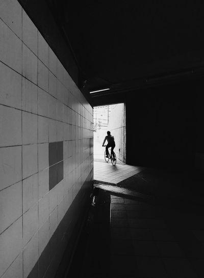 Silhouette man walking on footpath in tunnel