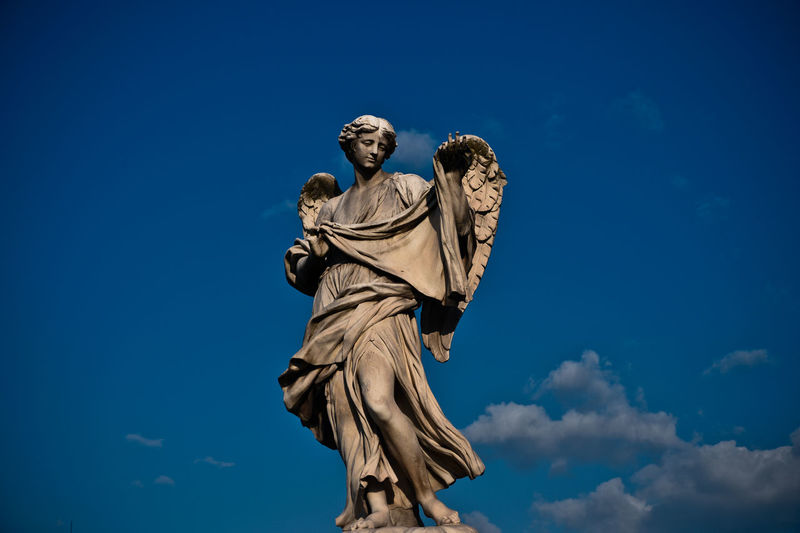 Low Angle View Of Statue Of Angel Against Clear Sky