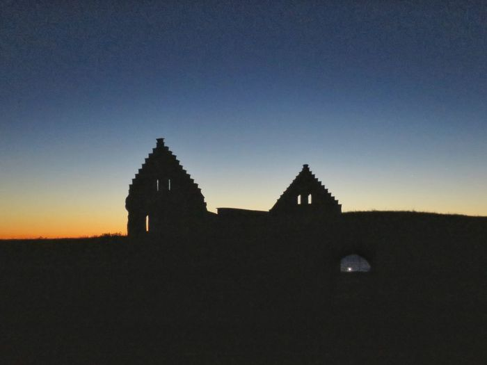Silhouette built structure against clear blue sky