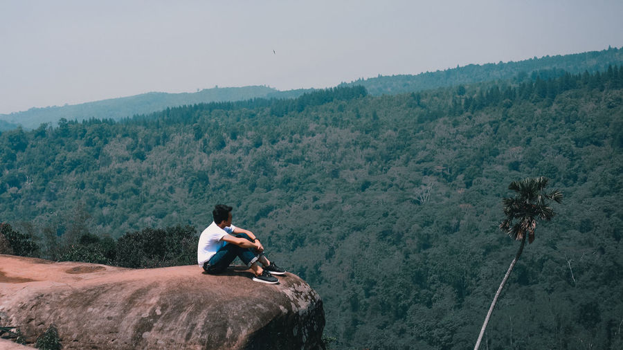 Man sitting on rocky mountains