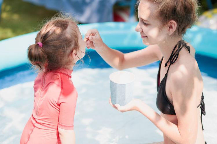 Siblings having ice cream in wading pool