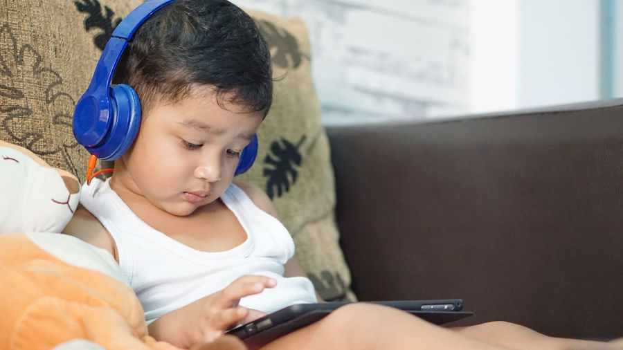 Boy using mobile phone while sitting on bed at home