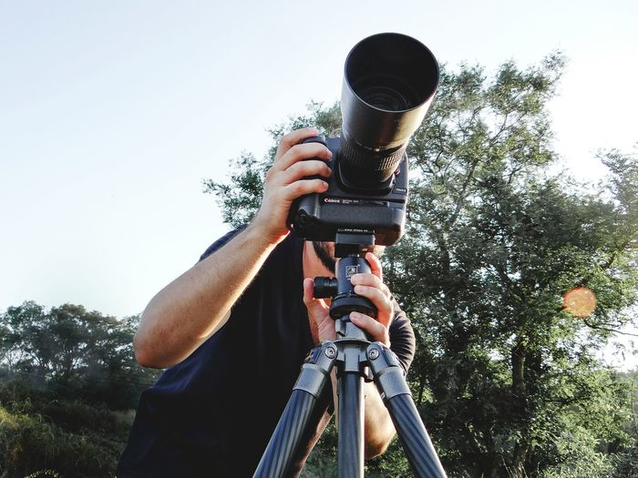 Low angle view of man photographing against sky