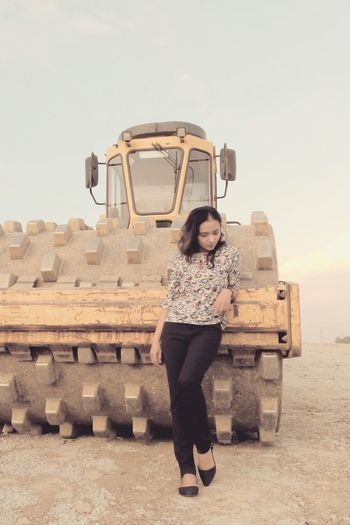 Full length of young woman standing by construction vehicle on field