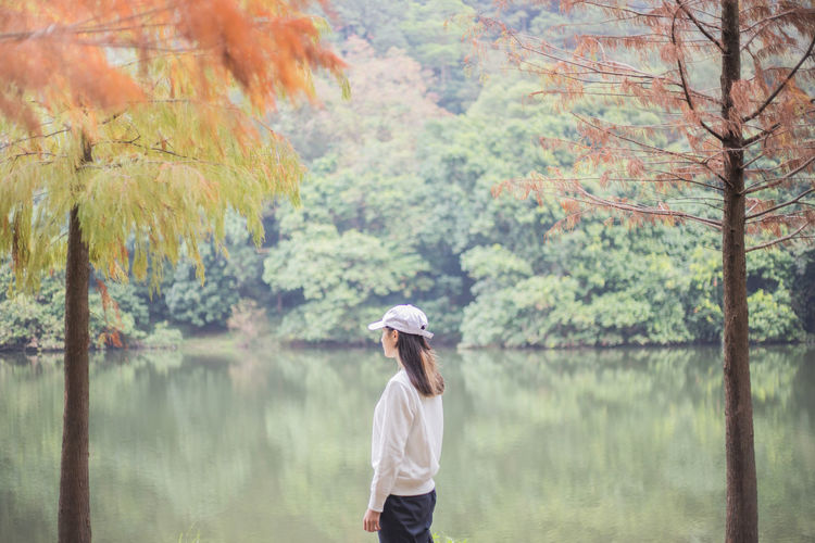 Tree One Person Standing Plant Autumn Nature Forest Casual Clothing Adult Day Land Waist Up Young Adult Clothing Water Change Focus On Foreground Hat Outdoors Rain Hairstyle