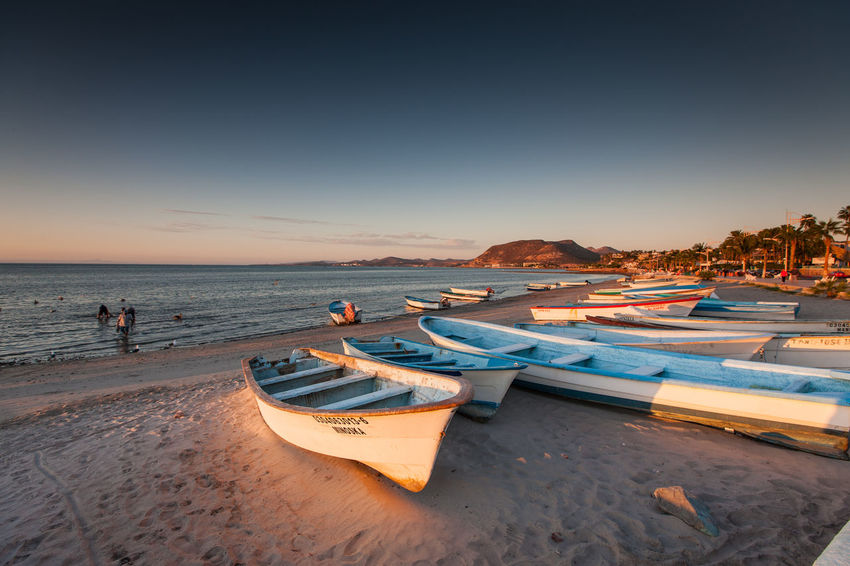 Panga fishing boats on the beach in La Paz, Mexico. Baja California Sur La Paz Baja California Sur Beach Beauty In Nature Boat Clear Sky Fishing Fishing Boat Horizon Over Water Mode Of Transportation Moored Nautical Vessel Outdoors Panga Sand Scenics - Nature Sea Sea Of Cortez Sky Sunset Transportation Water
