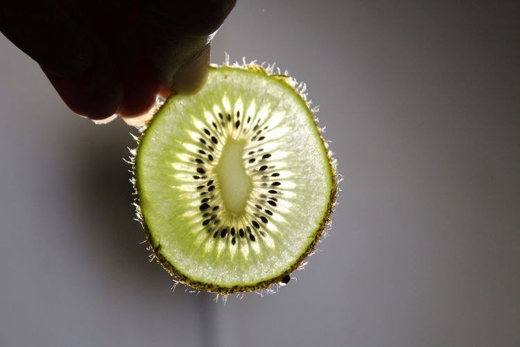 Cropped Hand Holding Kiwi Slice Against Wall