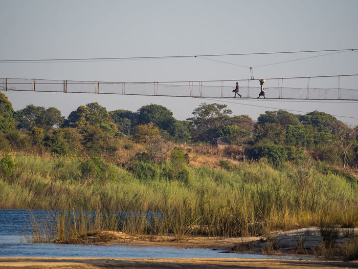 Scenic view of local people walking on foot bridge over zambezi river, zambia