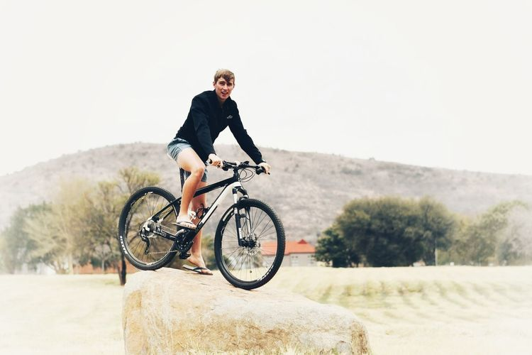 Full length of man riding bicycle against sky