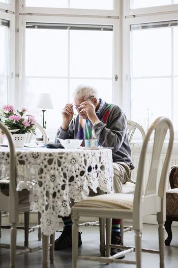 Full length of men sitting on table at home