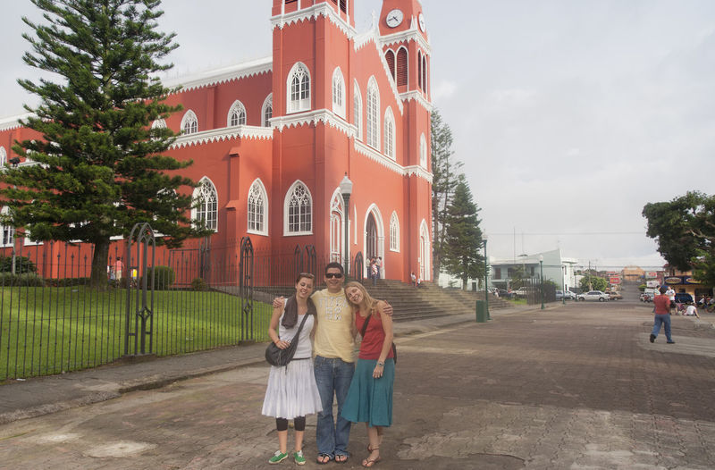 Young Adults in front of the Cathedral de la Mercedes in Grecia, Costa Rica Architecture Arm Around Bonding Building Exterior Cathedral Cathedral De La Mercedes Christianity Church Costa Rica Family Friendship Full Length Grecia Happy Landmark People Posing Religion Smile Three People Togetherness Tourist Travel Destinations Tropical Climate Young Adult