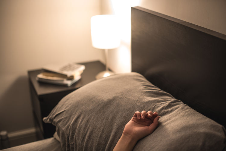 Cropped Hand Of Woman On Bed At Home