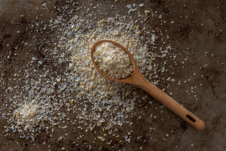 Directly above shot of grounded garlic and salt in wooden spoon on granite table