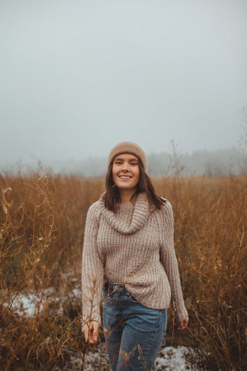 Portrait of smiling young woman standing on field against sky during winter
