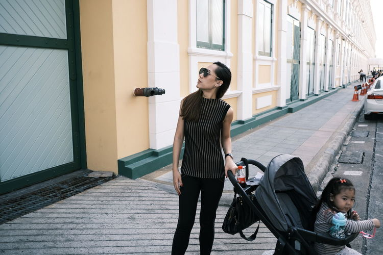 Woman standing with baby carriage in city