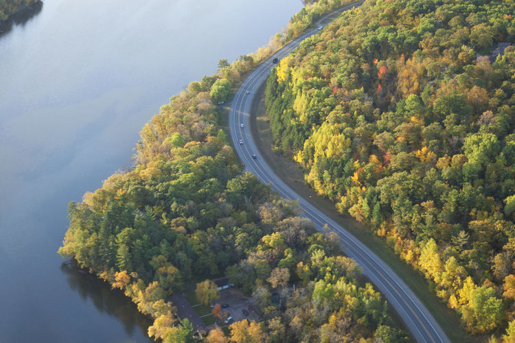 Aerial view of curving road along the Mississippi River in northern Minnesota on a bright autumn morning Aerial View Road Mississippi River Autumn Morning Light Curving Road Sunlight And Shadow Trees Color Landscape Water High Angle View Sunrise Cars Truck North Minnesota Copy Space Fall Beauty In Nature