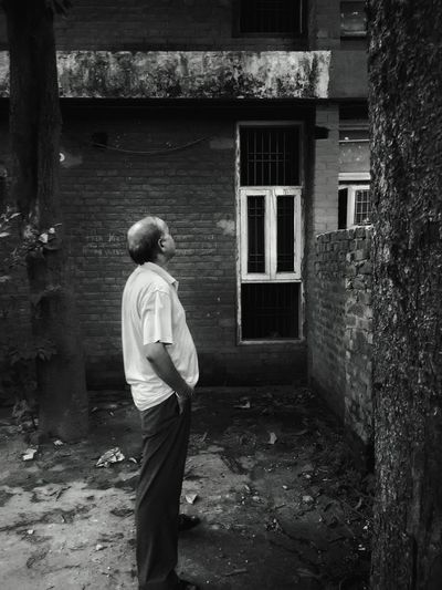 Side View Of Senior Man Standing By Old Building