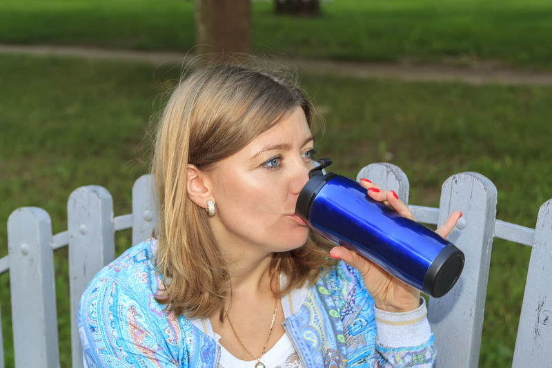Close-up of woman drinking water sitting outdoors