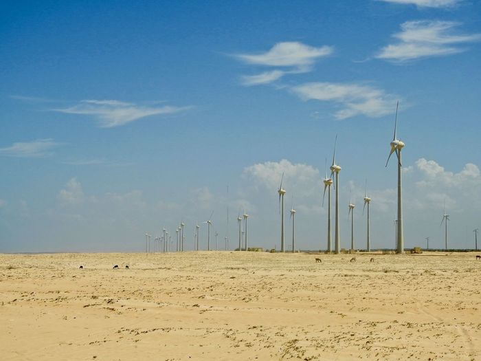 Scenic view of beach against sky with eolic turbines