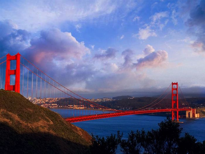 Golden Gate Bridge Over River Against Cloudy Sky