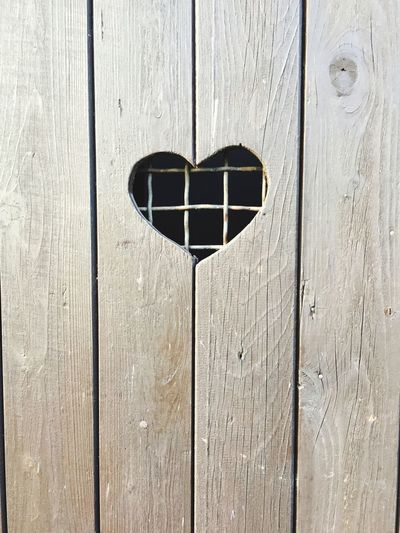 Close-up of wooden door with heart shape peephole