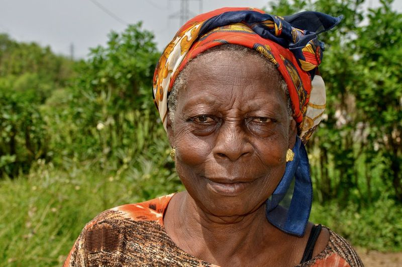 Portrait Headshot One Person Senior Adult Focus On Foreground Lifestyles Front View Real People Looking At Camera Adult Close-up Outdoors Smiling Africa Ghana Faces Of Africa Developing Country Poverty Social Issue Portrait Of A Woman Headscarf Nature Wrinkles Friendly Faces
