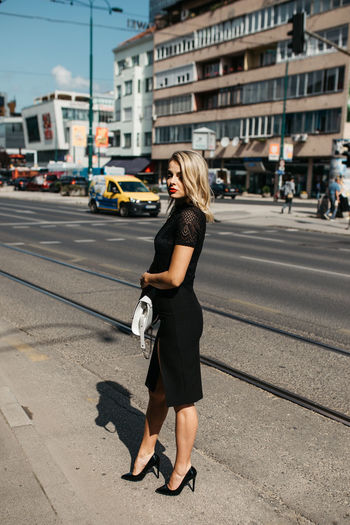 Fashionable woman standing against buildings in city