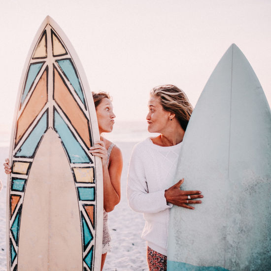 Two People Women Casual Clothing Adult Couple - Relationship Togetherness Men Leisure Activity Young Adult Lifestyles People Standing Real People Males  Young Women Young Men Heterosexual Couple Mid Adult Emotion Positive Emotion Surfboard Surfing Funny Funny Faces