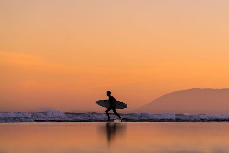 Silhouette man standing on shore against orange sky