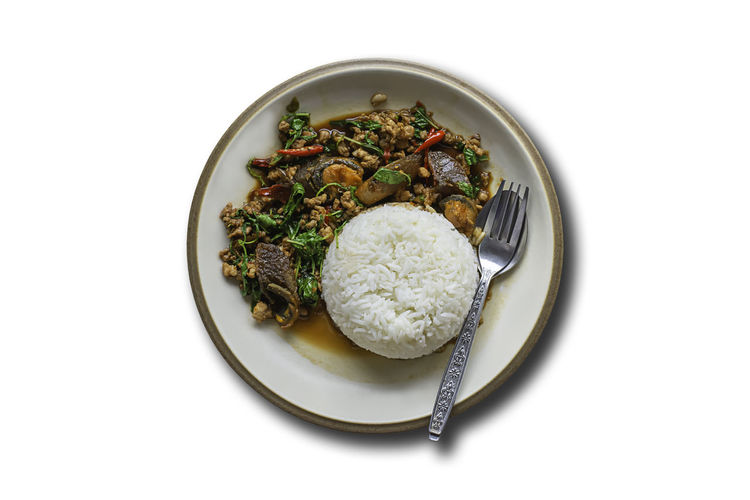 Stir fried basil leaf pork with rice and put the preserved egg on a white background with clipping path. White Background Cooked Isolated ASIA Asian  Background Basil Chicken Chili  Chilli Closeup Cooking Cuisine Delicious Dinner Dish Eat Food Fresh Fry Green Healthy Herb Hot Leaf Leaves Lunch Meal Meat Minced Pepper Plate Pork Red Restaurant Rice Spicy Steamed  Stir Stir-fried Street Tasty Text Thai Thailand TOPPED Traditional Vegetable White Wooden