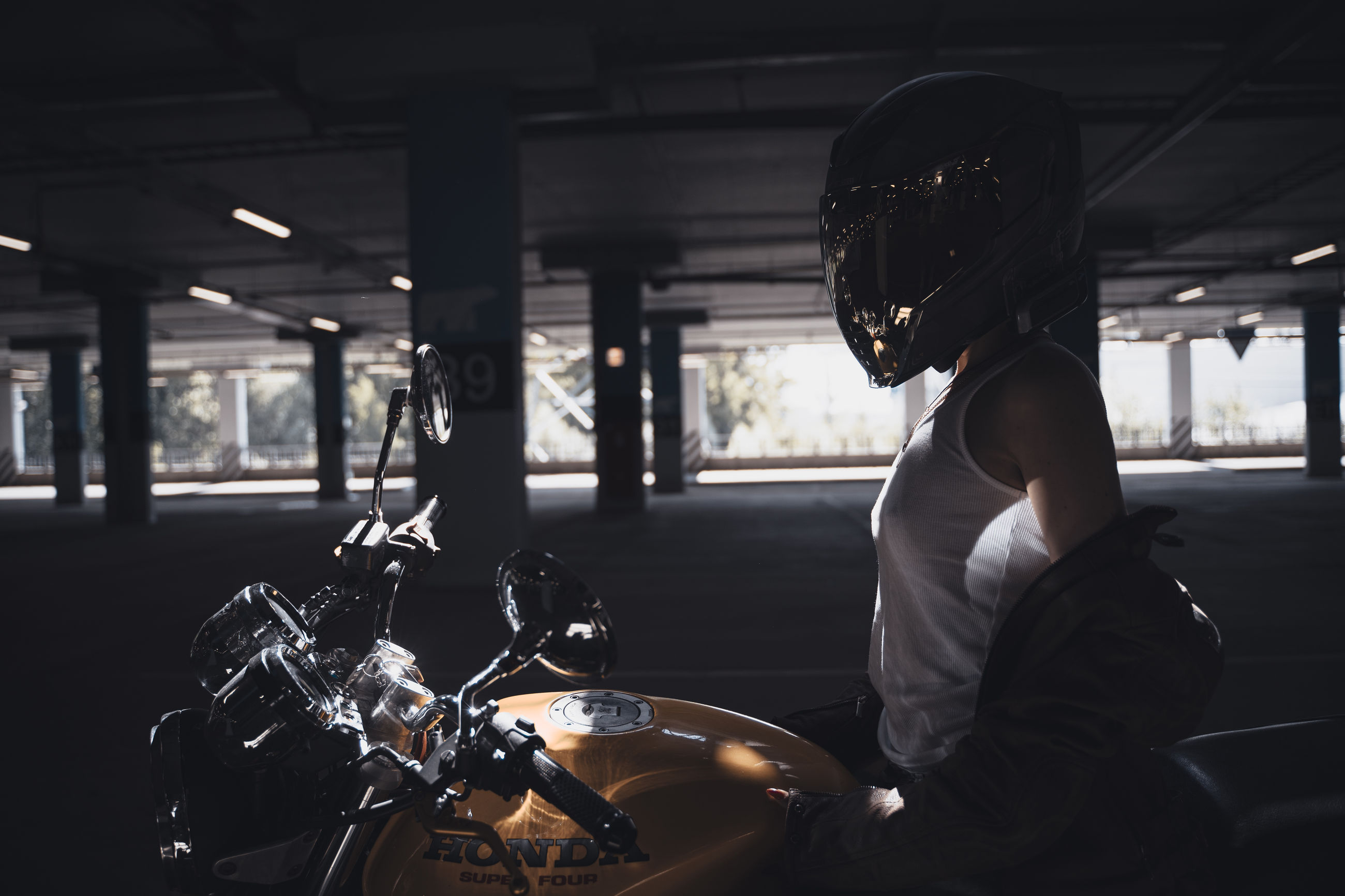 transportation, mode of transportation, one person, motorcycle, adult, vehicle, land vehicle, black, indoors, lifestyles, helmet, sports, women, headwear, side view, sports helmet, person, biker, crash helmet, clothing, architecture, night, car, auto part, young adult, darkness, leisure activity, men