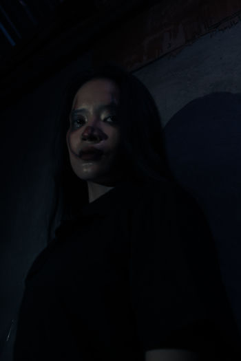 Portrait of smiling young woman standing in the dark