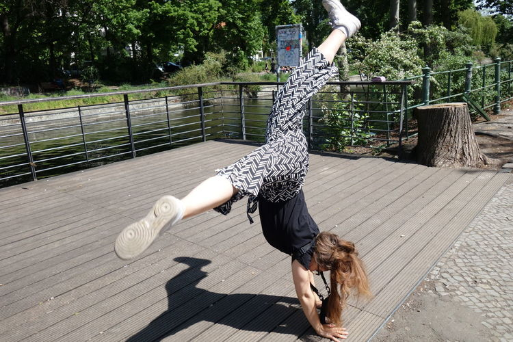 Full length shot of young woman doing cartwheel