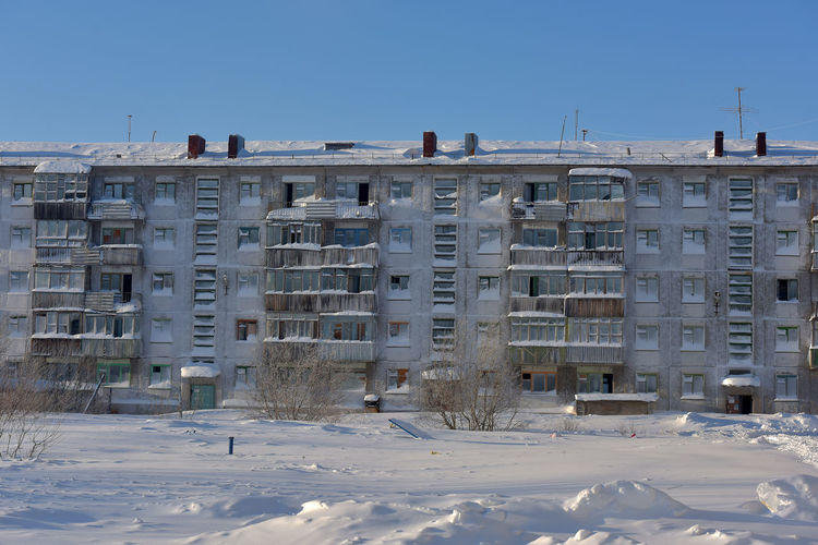 Buildings on snow covered field against sky
