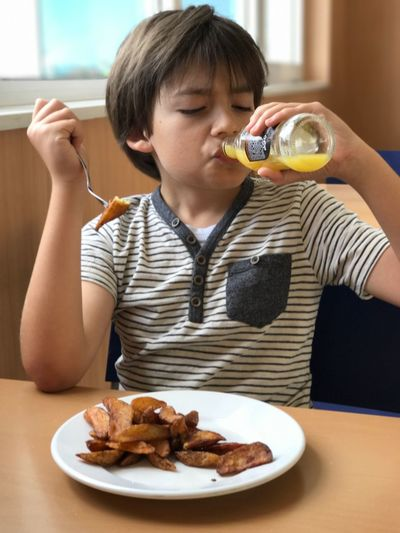 Boy drinking juice from bottle while sitting on chair at restaurant
