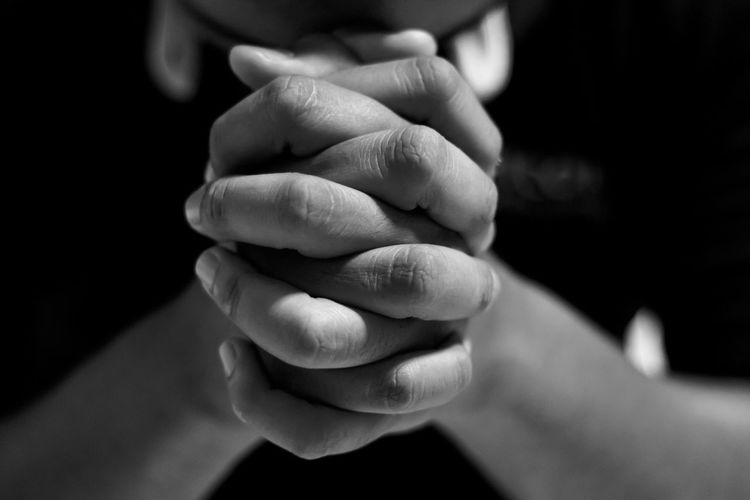Depressed man close up hands is praying for hope and encouragement to continue living