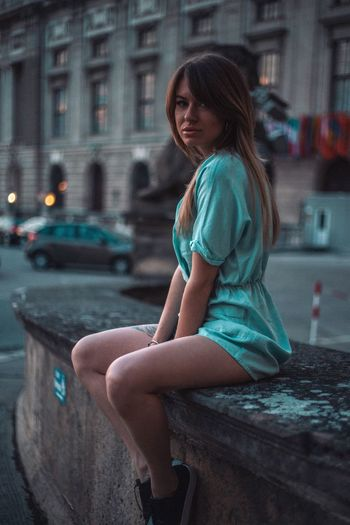 Side view of woman sitting in city