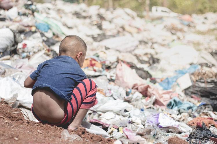 Rear view of boy sitting on garbage