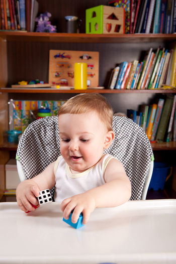 Cute baby boy playing with toy blocks on table