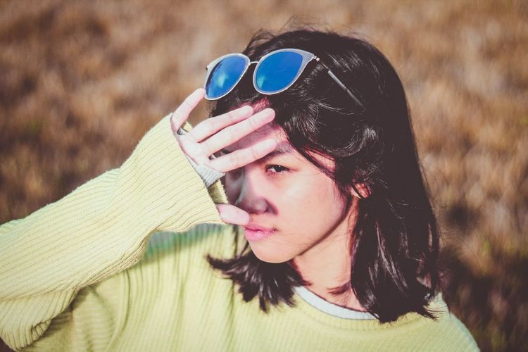 Young Woman Wearing Sunglasses On Field