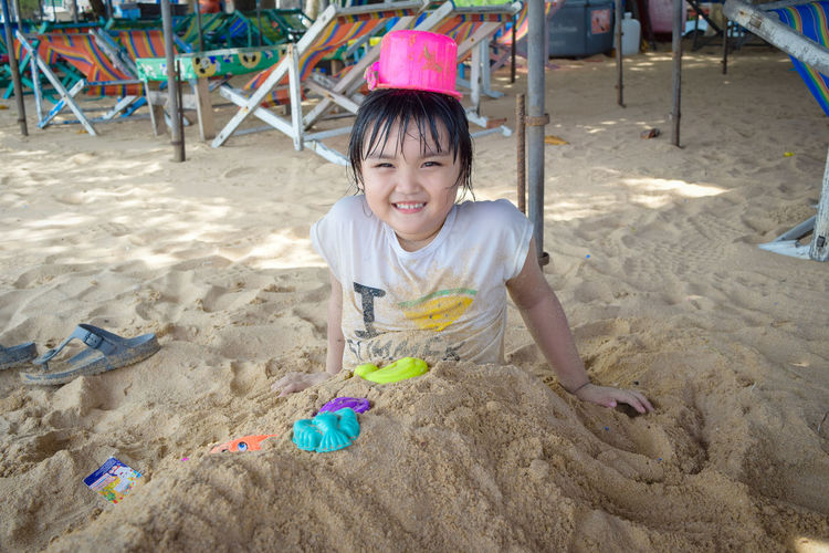 Portrait of smiling girl buried in sand at beach