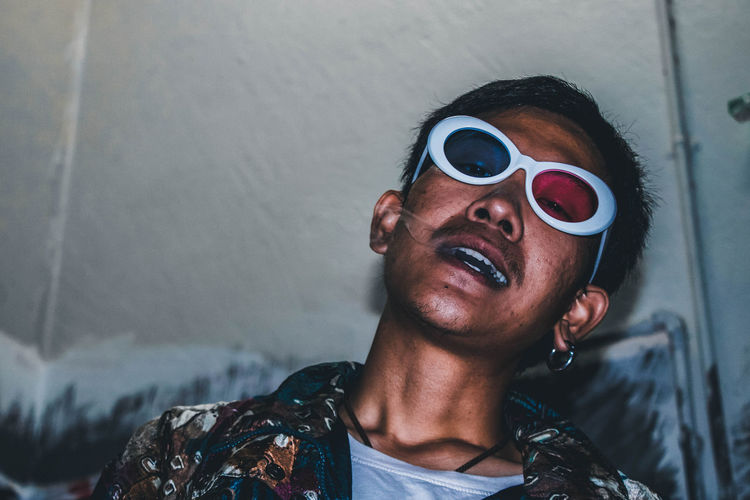 Portrait of young man wearing 3-d glasses while smoking cigarette