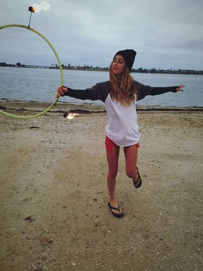 Full Length Of Young Woman With Fire Hula Hoop At Beach Against Sky