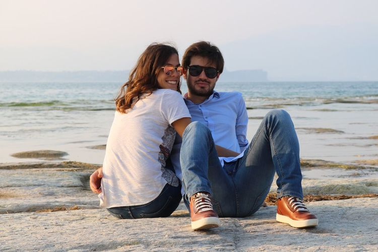Portrait Of Loving Young Couple Sitting On Rock At Beach
